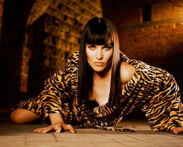 ca. 1998 --- Lucy Lawless Reclining in Tiger Print Robe --- Image by © Michael O'Neill/CORBIS OUTLINE